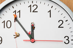 Miniature people climbing a clock. Four miniature people climbers ascending clock hands Royalty Free Stock Images