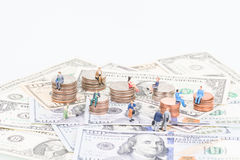 Miniature people on the coins and banknotes Royalty Free Stock Photos