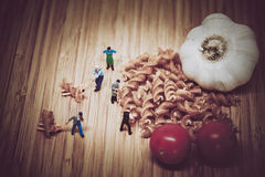Miniature people collect ingredients to cook pasta. Color tone t Royalty Free Stock Photography