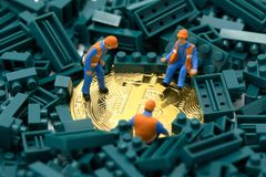 Miniature people Construction worker digs a gold bit coin in the middle of a green jug block. Communications to Invest in the Digi Royalty Free Stock Photography