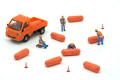 Miniature people Construction worker Load up the car model orange capsule medicine. on white background using as background. Business concept and Health concept royalty free stock photos