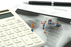 Miniature people Construction worker on white calculator with Lung x-ray .using as background Healthcare concept and Medical conce. Pt with copy space and white stock photo