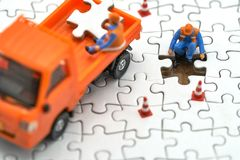 Miniature people Construction worker on white Jigsaw. using as background business concept and finance concept with copy space fo stock photos