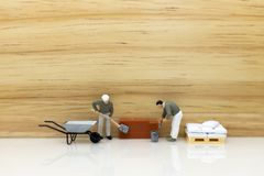 Miniature people: Construction workers building plans , have building materials, sand, brick, mortar. Use image for construction. Business stock photos