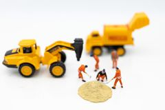 Miniature people: Construction workers building plans , have building materials, sand, brick, mortar. Use image for construction. Business royalty free stock image