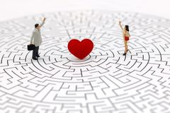 Miniature people: Couple standing on center of maze with red heart. royalty free stock photography