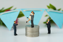 Miniature people with couple standing on top stack of coins and Royalty Free Stock Image
