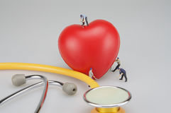 Miniature people cure heart and stethoscope Stock Photo