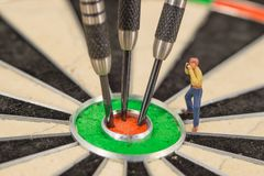 Miniature people with dart in bull& x27;s eye, close up. Concept stock photo