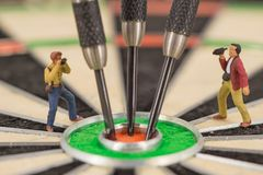 miniature people with dart in bull& x27;s eye, close up Royalty Free Stock Photo