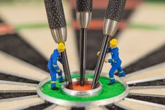 miniature people with dart in bull& x27;s eye, close up Royalty Free Stock Photos