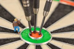 Miniature people with dart in bull& x27;s eye, close up. Concept royalty free stock photo