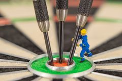Miniature people with dart in bull& x27;s eye, close up. Concept stock image