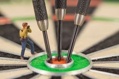 Miniature people with dart in bull& x27;s eye, close up. Concept stock images