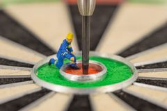 Miniature people with dart in bull& x27;s eye, close up. Concept royalty free stock photography