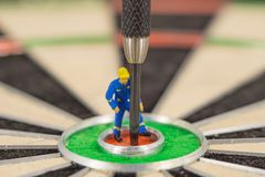 Miniature people with dart in bull& x27;s eye, close up. Concept royalty free stock photos