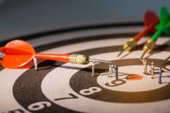 Miniature people  on dart. Teamwork concept Stock Images
