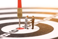 Miniature people on dartboard and shecking hand Stock Images