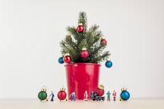 Miniature people decorating giant Christmas tree royalty free stock image