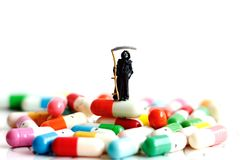 Miniature people: Demon of death standing on drugs. stock images