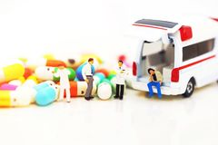 Miniature people: Doctor and patient standing with ambulance and drugs. royalty free stock photography