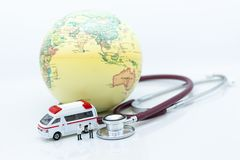 Miniature people, Doctor with stethoscope and world map, ambulance . Image use for health medical care of people concept.  Royalty Free Stock Photo