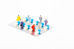 Miniature people with drug capsule Stock Image