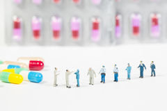 Miniature people on the drugs or pils on white Stock Image