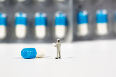 Miniature people on the drugs or pils on white Stock Photos