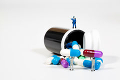 Miniature people on the drugs or pils on white Royalty Free Stock Images