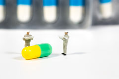 Miniature people on the drugs or pils on white Royalty Free Stock Photo
