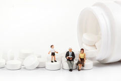 Miniature people - Elderly people posing in front of pills. Isolated on a white background stock photography