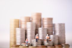 Elderly people sitting on coins stack. Retirement planning. stock images