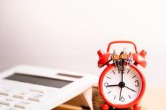 Miniature people: Elderly people sitting on red alarm clock. royalty free stock photos