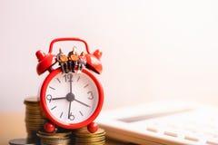 Miniature people: Elderly people sitting on red alarm clock. stock images