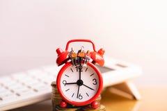 Miniature people: Elderly people sitting on red alarm clock. stock photography