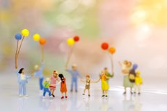 Miniature people, family and children with colorful balloons standing in front of house,. Family concept royalty free stock image