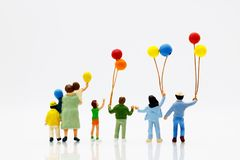 Miniature people, family and children enjoy with colorful balloo. Ns, happy family day concept Royalty Free Stock Images