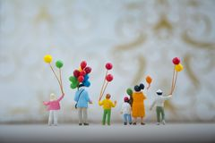 Miniature people: family and children enjoy with colorful balloons. Happy family day concept royalty free stock images