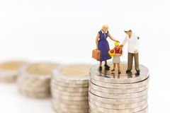 Miniature people, Family figure standing on top of stack coins . Image use for Life insurance concept.  Royalty Free Stock Images