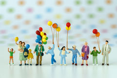 Miniature people with family holding balloon with pop color dot. Background as happy family concept stock photos