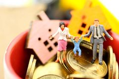 Miniature people : Family with Mini house with gold coins,mortg. Age , loans, management property concept royalty free stock image