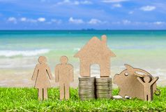 Miniature People Family with Stack Coins. On grass floor.selective focus Stock Images