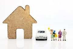 Miniature people with family standing with houses and car, happy stock photography