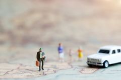 Miniature people: Family walking hand in hand with on world map royalty free stock image