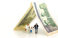 Miniature people: Family walking with money using as family security concept.  Royalty Free Stock Image