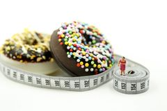 Miniature people : Fat woman and friend with Donut tying by measuring tape,dietary for slim shape concept.  stock photo