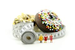 Miniature people : Fat woman and friend with Donut tying by measuring tape,dietary for slim shape concept.  royalty free stock photography