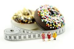 Miniature people : Fat woman and friend with Donut tying by measuring tape,dietary for slim shape concept.  stock photos