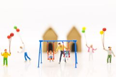 Miniature people : father swing cradle with children, and childrens play balloon together wiht fun. Using as background International day of families concept stock photography